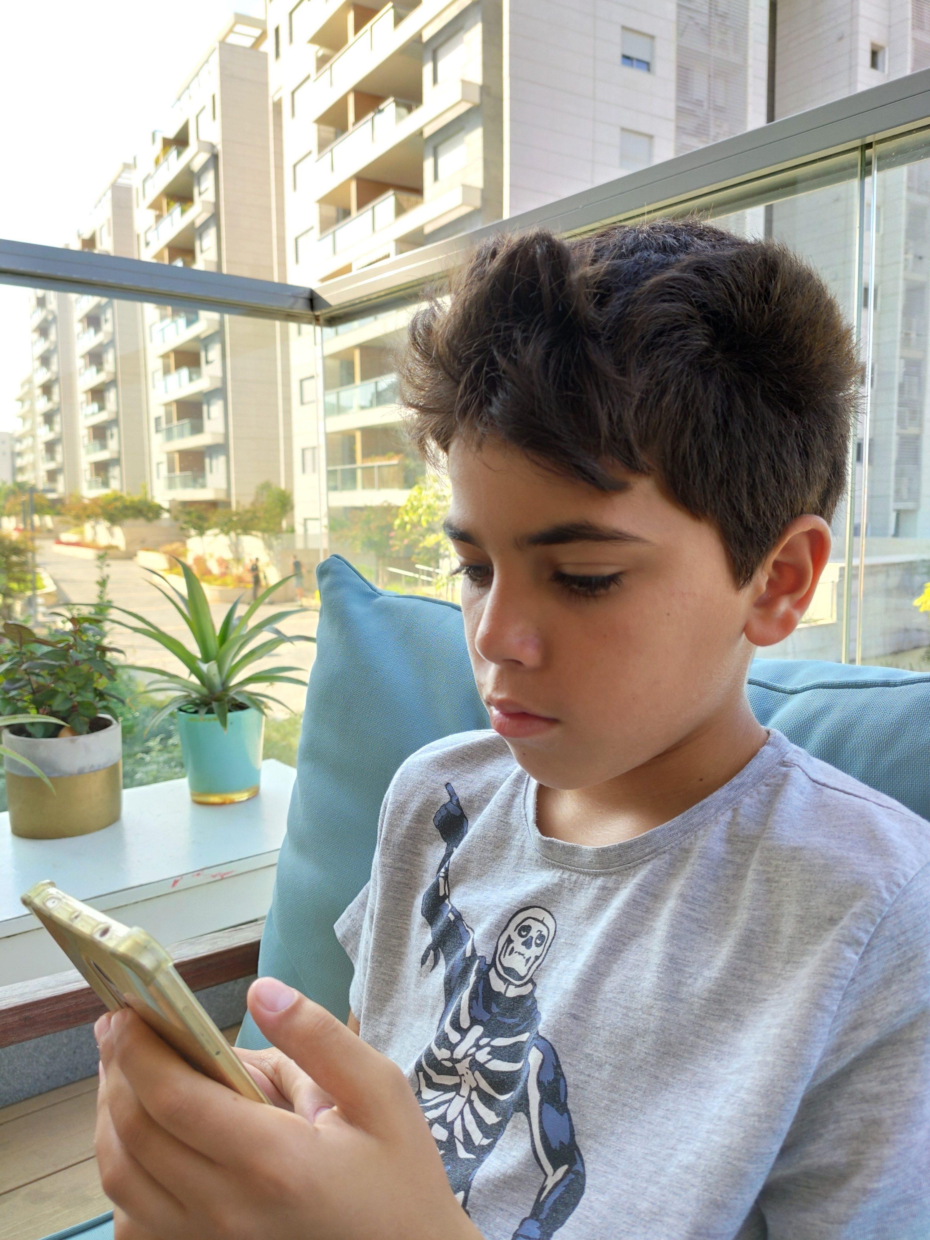 ילד מחזיק סלולר - סלולרי לילד